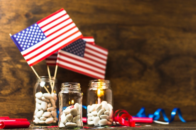 Eua bandeira americana e velas acesas no branco doces jarra na mesa de madeira