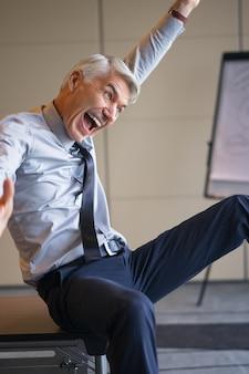 Eufórico, entusiástico homem de negócios sênior gesticular