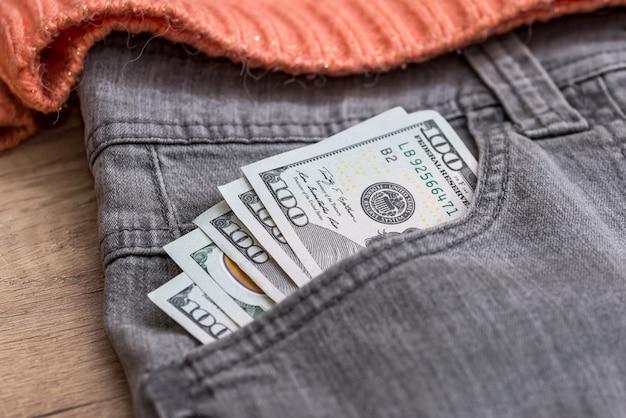 Euro dólares no bolso cinza do jeans