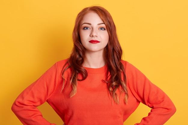 Europeia jovem ruiva linda em suéter laranja casual olhando para a câmera com expressão facial calma