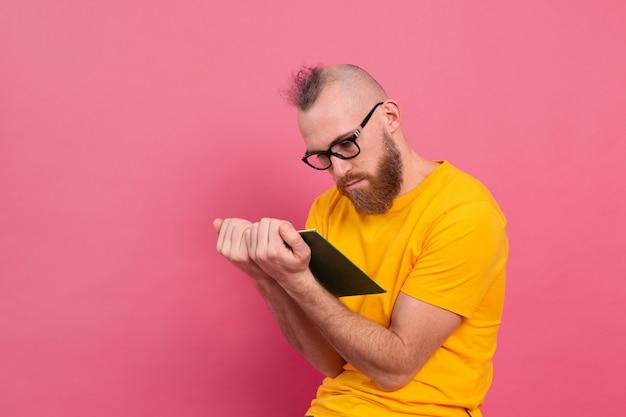 Europeu adulto barbudo de óculos lendo livro isolado na rosa
