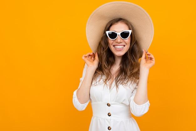 Europeu alegre elegante em um chapéu em uma superfície laranja