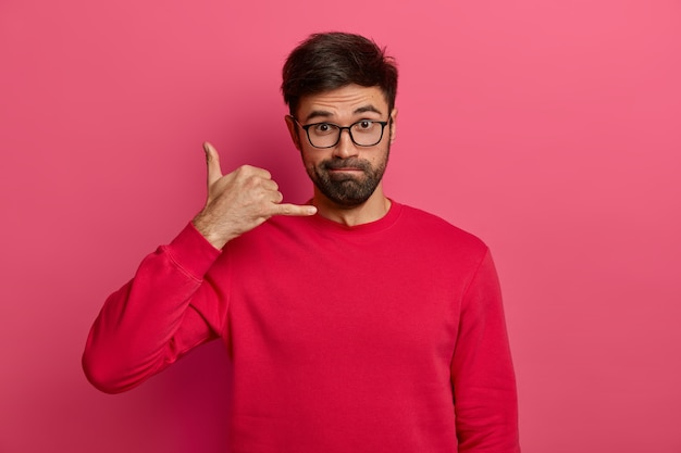 Europeu com a barba por fazer séria faz gesto de me ligar de volta, está sempre em contato, usa óculos transparentes e suéter vermelho, pede telefone, isolado em parede rosa.