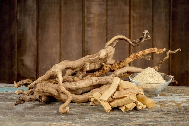 Eurycoma longifolia jack, raízes secas e pó em um velho fundo de madeira.