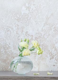 Eustoma amarelo em vaso de vidro na mesa