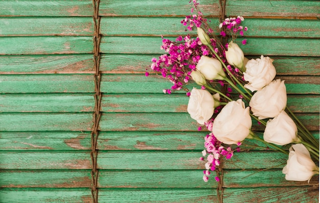 Eustoma e flores de respiração do bebê contra o fundo do obturador de madeira verde