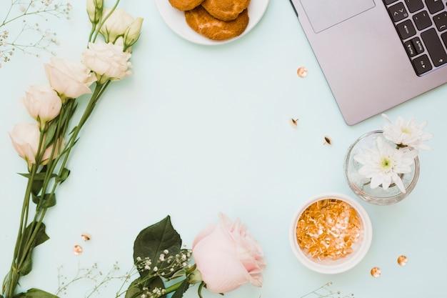 Eustoma e rosa flores com biscoitos; pino de ouro; e laptop no fundo azul pastel