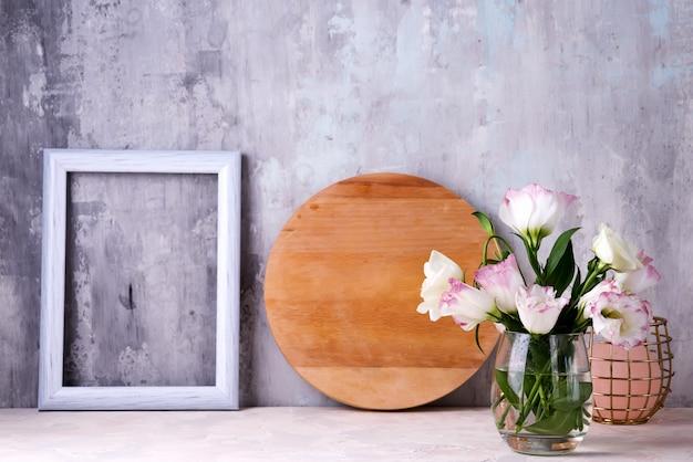 Eustoma floresce no vaso na mesa perto da parede de pedra, espaço para texto.