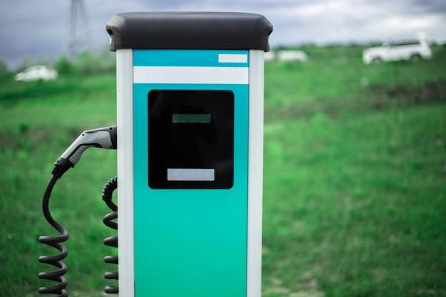 Ev, estação de carregador de carro elétrico na grama verde