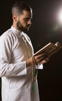 Evento de ramadam e homem árabe em pé com alcorão e contas de oração