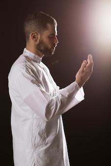 Evento de ramadam e homem árabe rezando e de pé lateralmente