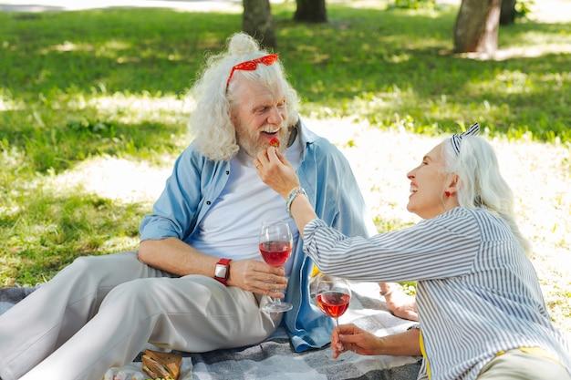 Evento prazeroso. pessoas alegres e alegres sorrindo umas para as outras enquanto desfrutam de seu piquenique romântico