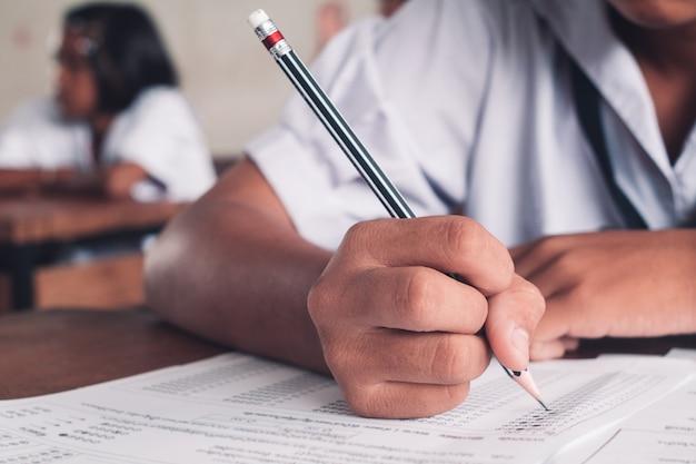 Exame com estudante da escola uniforme fazendo teste educacional com estresse em sala de aula