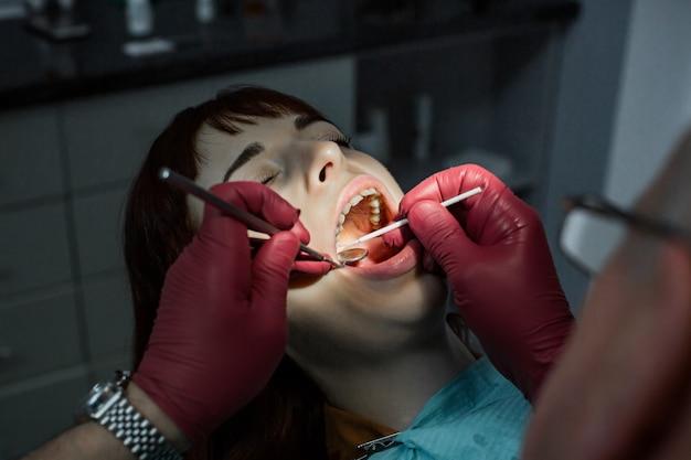 Exame dentário extenso. feche acima do tiro de uma jovem mulher que tem os dentes examinados por um dentista profissional usando luvas médicas vermelhas. conceito oral dental