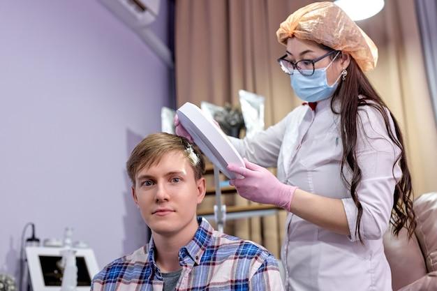 Exame dermatológico do couro cabeludo e dos folículos capilares de um jovem paciente do sexo masculino, branco, em uma clínica de cosmetologia.