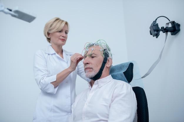Exame eeg. neurologista feminina ajustando a tampa do eletrodo na cabeça de um paciente masculino de cabelos grisalhos
