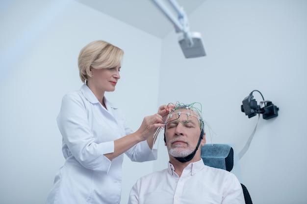 Exame eeg. neurologista feminina colocando uma tampa de eletrodo na cabeça de um paciente masculino de cabelos grisalhos