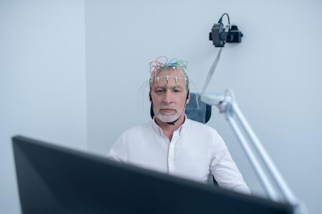 Exame eeg. paciente masculino grisalho submetido a eletroencefalograma