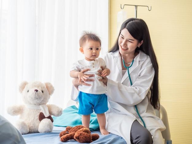 Exame médico bonito um menino na cama do paciente.