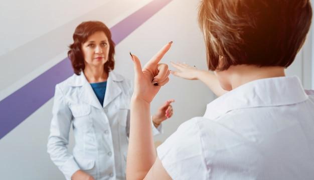 Exame neurológico. o neurologista testando reflexos em uma paciente do sexo feminino usando um martelo.