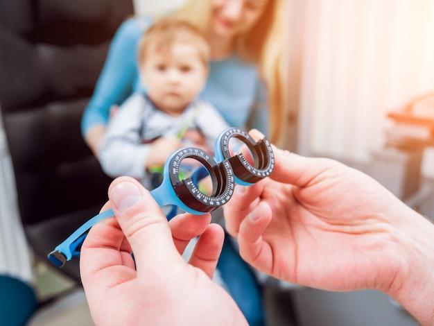 Exame oftalmológico básico. mãe mantém filho durante o exame oftalmológico.