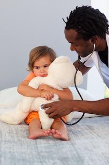 Exames de pediatra, uma pequena garota com estetoscópio