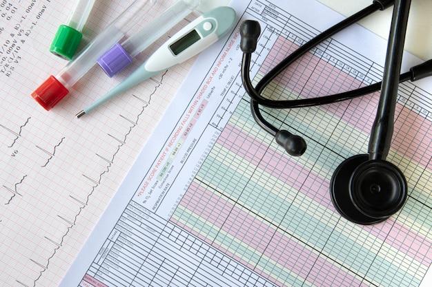 Exames de sangue, um termômetro digital e um estetoscópio em cima de uma mesa
