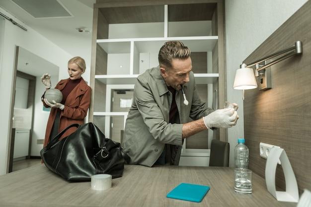 Examinando o cientista criminoso. cientistas forenses executivos examinam a sala com equipamentos especiais em busca de confirmação do crime