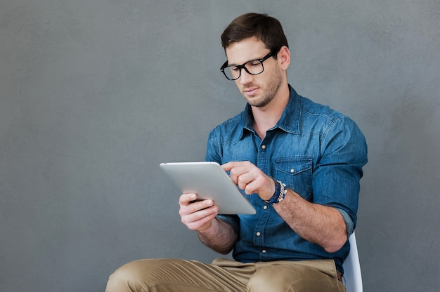 Examinando seu novo gadget. jovem confiante segurando um tablet digital