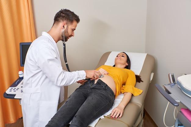 Examinando uma mulher grávida com um estetoscópio