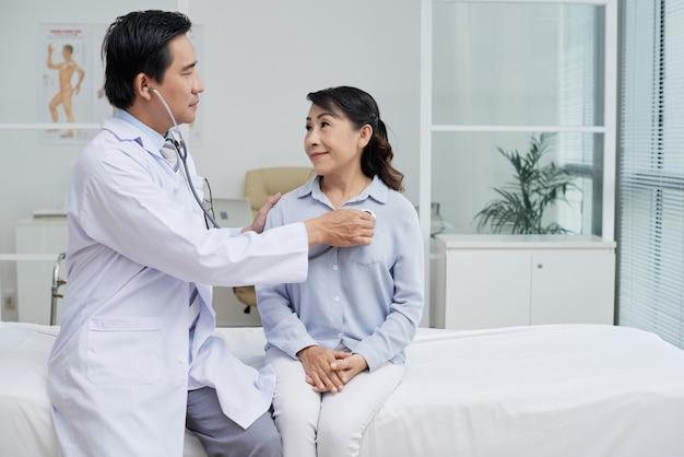 Examinar paciente sênior com estetoscópio