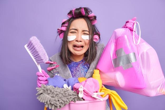 Exausta, chorando, dona de casa asiática segura saco de lixo de polietileno escova de limpeza faz lavanderia usa melhores detergentes tenta ficar bonita faz penteado encaracolado isolado sobre a parede roxa do estúdio