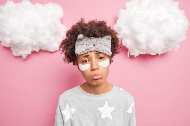 Exausta descontente triste mulher étnica com cabelo encaracolado cansa olhar depois de um dia agitado quer dormir usa máscara de dormir faz tratamentos faciais aplica compressas de colágeno isoladas sobre parede rosada