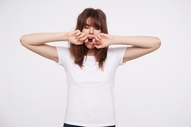Exausta, jovem senhora de cabelos escuros com maquiagem natural, mantendo os olhos fechados enquanto boceja com a boca bem aberta, mantendo as mãos levantadas enquanto posa sobre uma parede branca