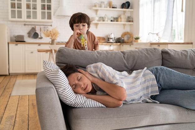 Exausta mãe caucasiana deitada no sofá com os olhos fechados, ouvidos tapados, cansada do comportamento do filho hiperativo