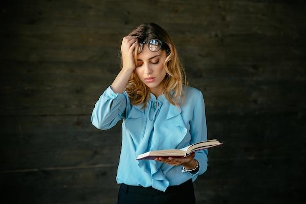 Exausta mulher parece cansada, detém um livro, mantém a cabeça com a mão