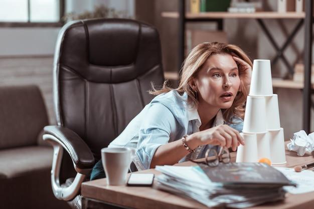 Exausto depois do trabalho. advogada loira de olhos azuis bem-sucedida sentindo-se cansada e exausta depois do trabalho