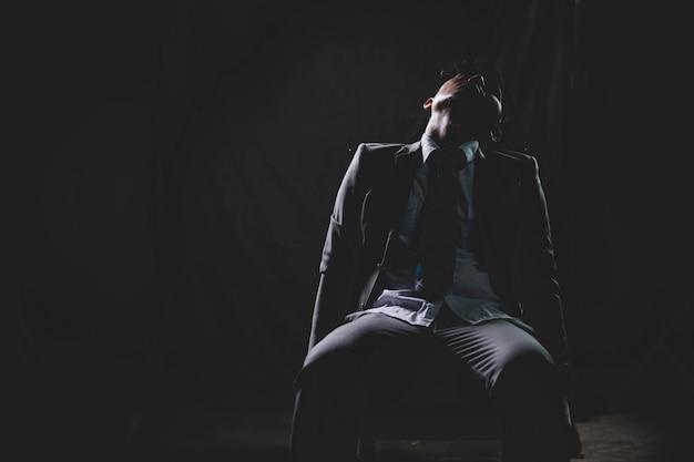 Exausto e cansado do homem de negócios asiático do excesso de trabalho, localização e dormir na cadeira no escuro.
