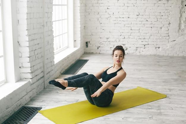 Exausto, jovem europeu realizando barco asana enquanto pratica ioga dentro de casa. menina morena sentada no tapete verde, fazendo pose de navasana com as costas e pernas levantadas e os braços estendidos para frente