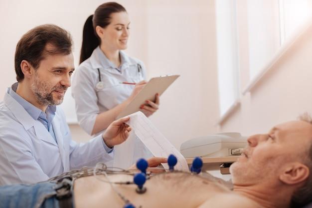 Excelente cardiologista competente fazendo um eletrocardiograma e ditando os resultados dele e a enfermeira anotando-os