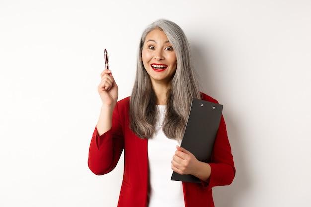 Excelente ideia. feliz empregador feminino asiático segurando a prancheta e levantando a caneta com um sorriso satisfeito, ouve uma sugestão interessante, em pé sobre um fundo branco.