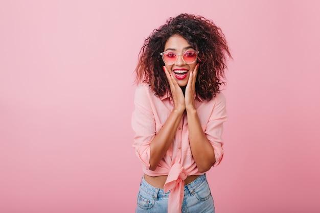 Excelente modelo africano que expressa emoções de surpresa durante a pose. mulher encaracolada elegante em óculos de sol se divertindo.