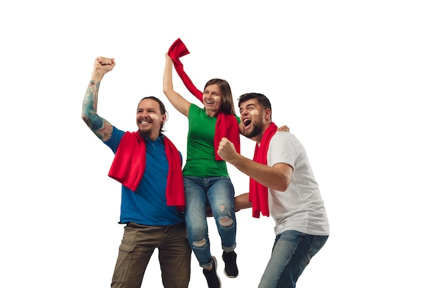 Excelente objetivo. três fãs de futebol, mulher e homens torcendo pelo time de esporte favorito, com emoções brilhantes, isoladas no fundo branco do estúdio. parecendo animado, apoiando. conceito de esporte, diversão, apoio.