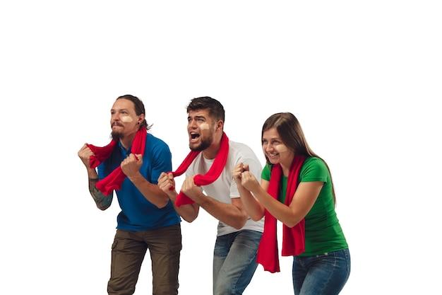 Excelente objetivo. três fãs de futebol, mulher e homens torcendo pelo time de esporte favorito com emoções brilhantes, isoladas no fundo branco do estúdio.
