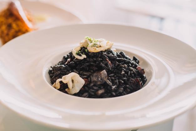 Excelente prato gourmet de frutos do mar estilo paella com tinta de lula e arroz preto em restaurante chique