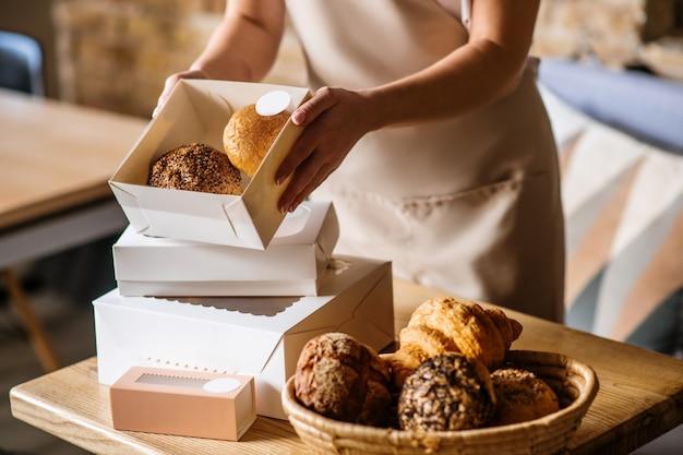 Excelente resultado. mãos femininas carinhosas segurando uma pequena caixa branca com tampa transparente com pãezinhos deliciosos