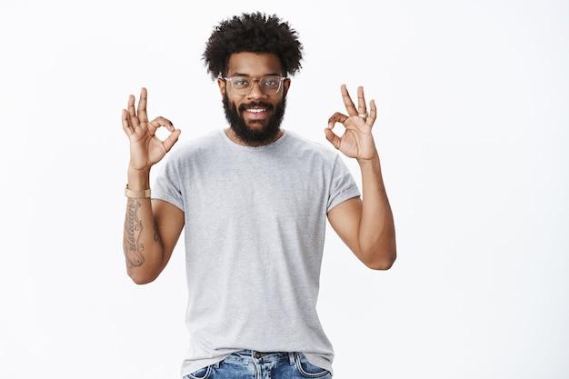 Excelente trabalho, orgulho de seu companheiro. retrato de homem barbudo afro-americano de aparência amigável e descolado, com tatuagens e piercing no nariz, mostrando gestos de ok e sorrindo satisfeito sobre a parede cinza