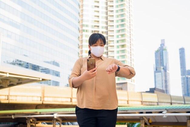 Excesso de peso mulher asiática com máscara usando telefone e verificar o tempo na ponte skywalk