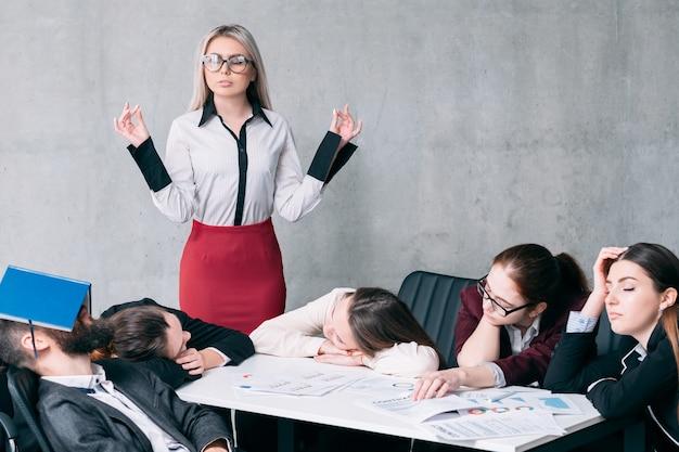 Excesso de trabalho da contabilidade anual. equipe de negócios cansada dormindo no local de trabalho. chefe chocado em pé com as mãos de mudra.