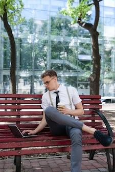 Excesso de trabalho. data limite. estilo de vida de negócios. homem segurando uma xícara de café sentado em um parque urbano com o laptop no banco